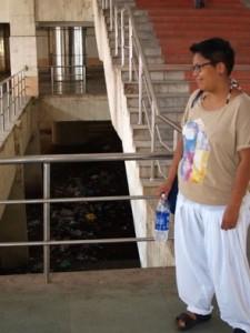 Sara framför den äckliga kanalen under tågstation i Adyar där vi bodde